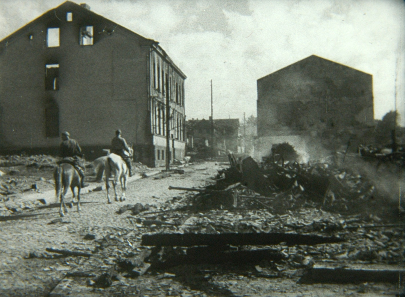 This event poster shows a still of two men on horseback passing by destroyed buildings in the city of Bialystok.